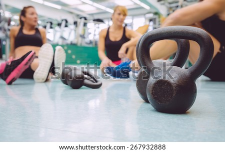 Closeup of black iron kettlebell and people group sitting on the floor of a fitness center in the background - stock photo