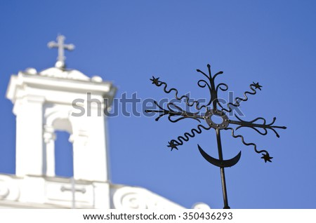 Closeup of black metal ornamental cross with a white church in the background