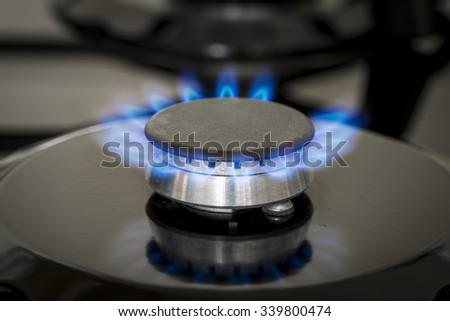 Closeup of black stove with gas flame  - stock photo