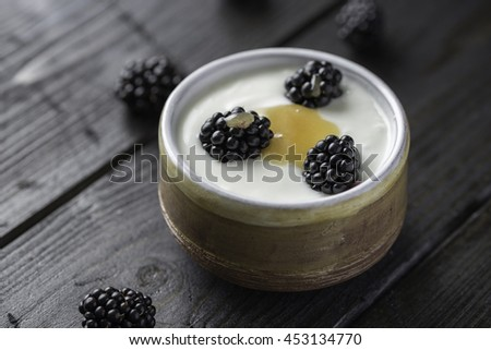 Closeup of blackberries with honey, white yogurt in brown bowl on black wooden table. - stock photo