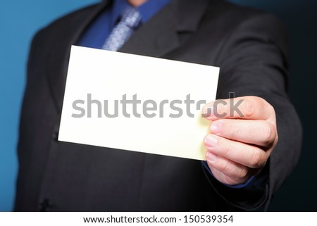 Closeup of blank business note card or signboard in man's hand blue background