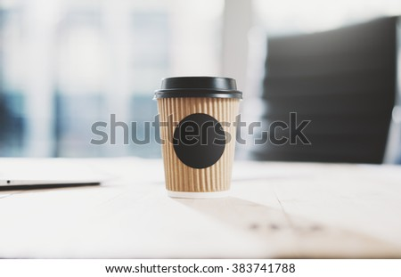 Closeup of blank craft paper coffee cup on the wood table. Space for you advertising. Horizontal mockup, blurred background - stock photo