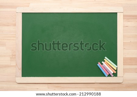 Closeup of blank green blackboard with pieces of coloured chalks on wooden surface. - stock photo
