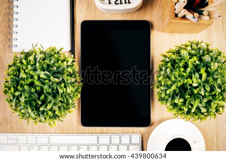 Closeup of blank tablet on wooden desktop with two plants, coffee cup, computer keyboard and stationery items. Mock up - stock photo
