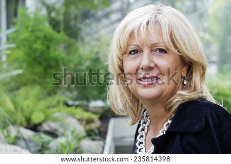 Closeup of Blond hair mature woman smiling and looking at camera outdoors. - stock photo