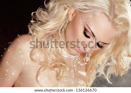 Closeup of blond sexy girl model in twinkled crystals on skin with curly hair and makeup. Jewelry. Brilliants. Diamonds - stock photo