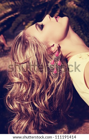 closeup of blond woman with long wet curly hair wearing pink lipstick and gold and pink neon earrings in summer sun - stock photo