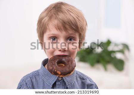 closeup of blonde boy eating doughnuts. portrait of cute little boy biting sweets - stock photo