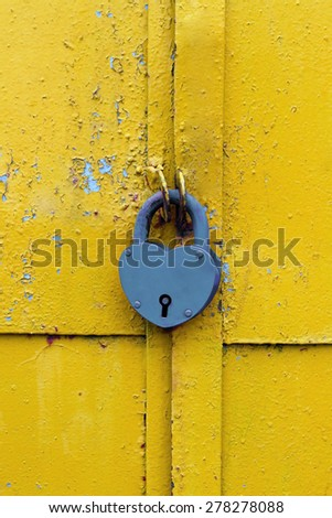 Closeup of blue lock on a rusty yellow door - stock photo