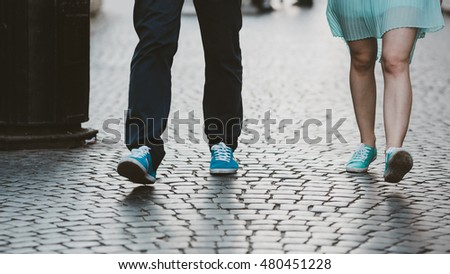 Closeup of blue sneakers in which walk young couple