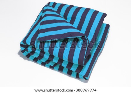 Closeup of blue striped comforter on white background - stock photo