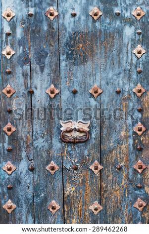 Closeup  of blue texture of wooden door with rusty design elements - stock photo