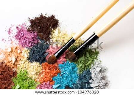 Closeup of blush and multicolor crushed eye shadows on white background - stock photo