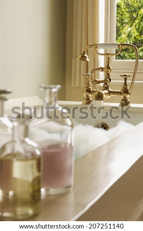 Closeup of bottles of bath oils on edge of bathtub with water running from tap - stock photo