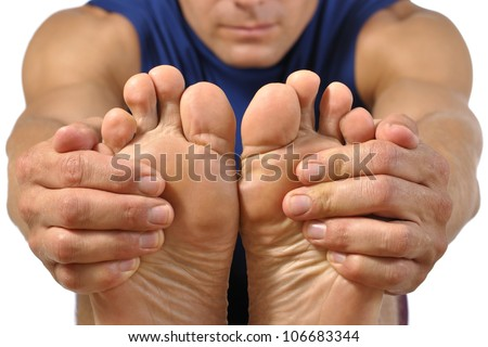 Closeup of bottom of bare feet of male athlete as he holds feet to do hamstring stretch on white background - stock photo