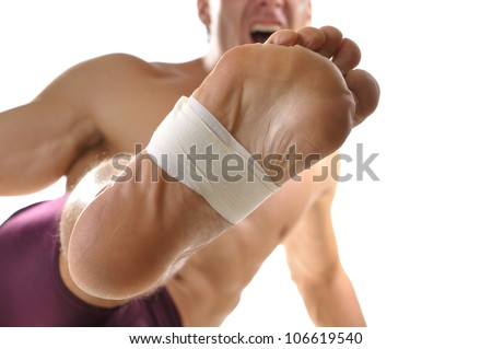 Closeup of bottom of man's foot with middle of foot wrapped with sports tape as he does martial arts kick on white background