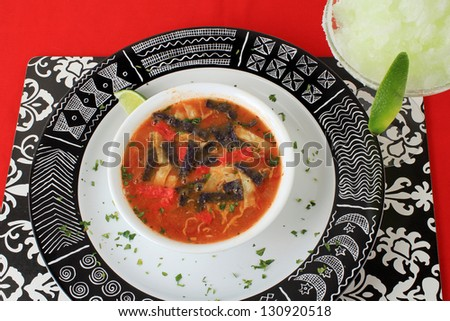 Closeup of bowl of tortilla soup on black and white plate of Mexican Aztec design on red place mat with frozen margarita. - stock photo