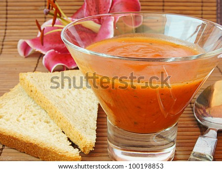 Closeup of bowls of delicious tomato soup and slice of bread