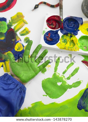 Closeup of boy's hand finger painting in art class - stock photo