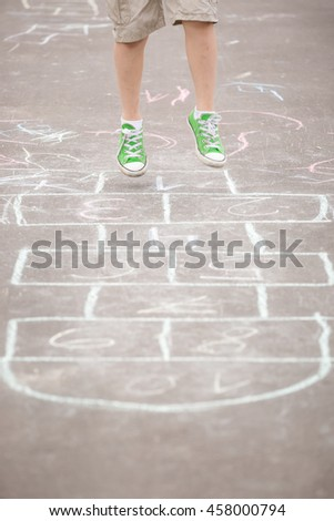 Closeup of boy's legs and hopscotch drawn on asphalt. Child playing hopscotch on playground outdoors on a sunny day. outdoor activities for children - stock photo