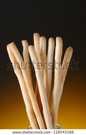Closeup of bread sticks against a light to dark warm background. Vertical Format.