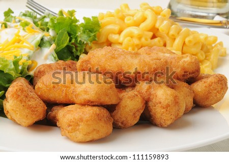 Closeup of breaded chicken strips with macaroni and cheese and salad