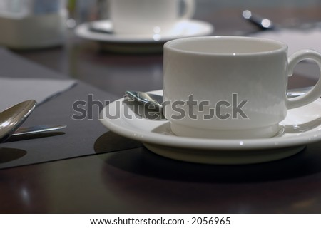 closeup of breakfast table with cup, spoon and knife