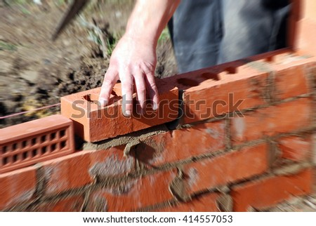 Closeup of bricklayer during the building of a house extension. Zoom effect applied centered on hand holding brick.