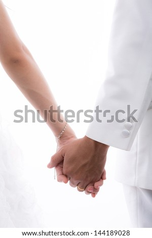 Closeup of  bride and groom holding hands isolated on white background - stock photo