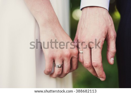 Closeup of bride and groom holding hands, wearing wedding rings on their fingers. Shallow focus.