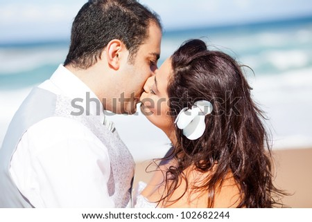 closeup of bride and groom kissing on beach - stock photo