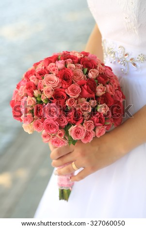 Closeup of bride holding with hand one big beautiful colorful soft aroma fresh wedding bouquet of many pink and purple rose flowers sunny day outdoor on natural background, vertical picture - stock photo