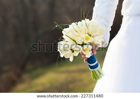 Closeup of bride's hand holding a wedding bouquet in autumn outdoors - stock photo