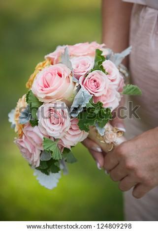 Closeup of bridesmaid holding wedding bouquet - stock photo