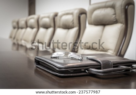 Closeup of briefcase on table in empty corporate conference room before business meeting in office