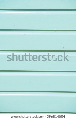 Closeup of bright empty wooden clapboard textured siding painted in light blue color with horizontal lines  - stock photo