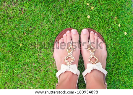 Closeup of bright flip flops and legs on green grass - stock photo