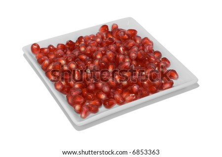 Closeup of bright red pomegranate seeds displayed in a square white dish.