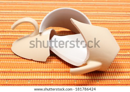 Closeup of broken cup, shattered cup, damaged mug lying on orange cloth - stock photo
