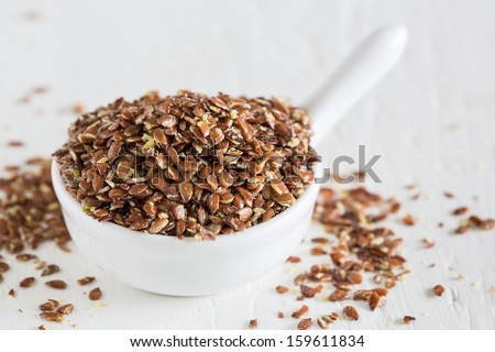 Closeup of broken flax seeds which contain a lot of fibre - stock photo
