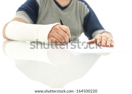 Closeup of broken male hand in plaster signing insurance claim. - stock photo