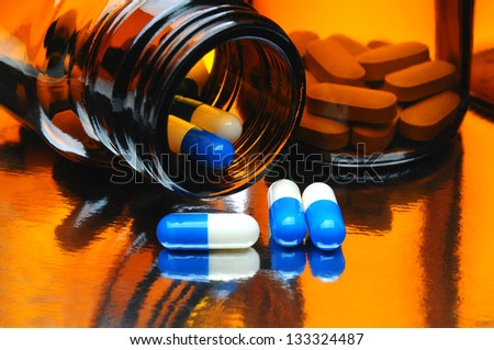 Closeup of Brown Medicine bottles with blue and white capsules and pills on a reflective surface. Horizontal format fills the frame.