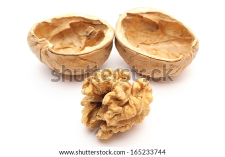 Closeup of brown walnut without shell and nutshells in background. Isolated on white background - stock photo