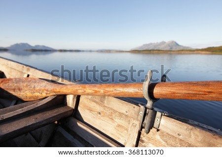 Closeup of brown wooden oar in rowing boat rowlock at sea in sunlight.  - stock photo