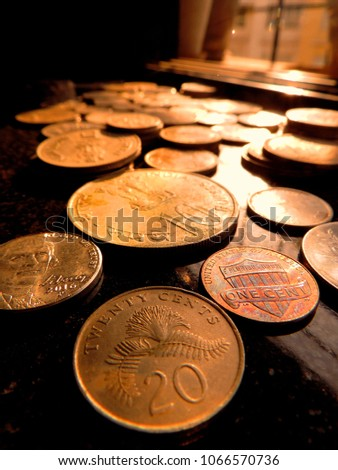 Closeup Of Bunch Of International Coins From Singapore 20 Cents Us 5 1 Cents Indian 10 Ruplaced On Black Background With Evening Golden Sunlight