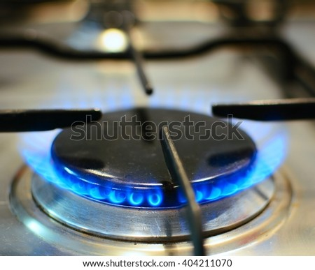 Closeup of burner with fire and flame on kitchen gas stove.  - stock photo