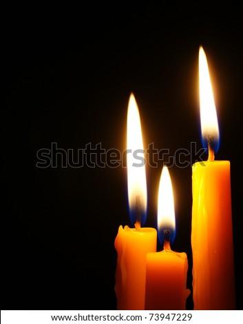 Closeup of burning candle isolated on black background. - stock photo