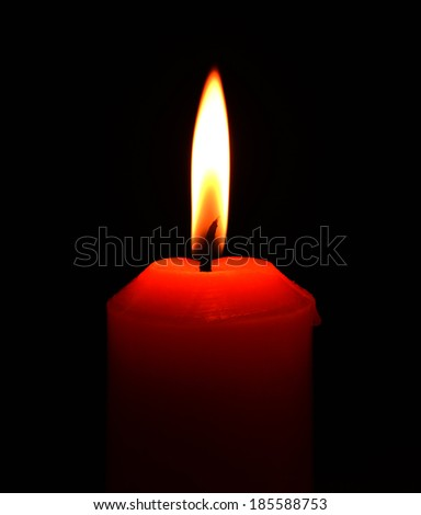 Closeup of burning candle on black background