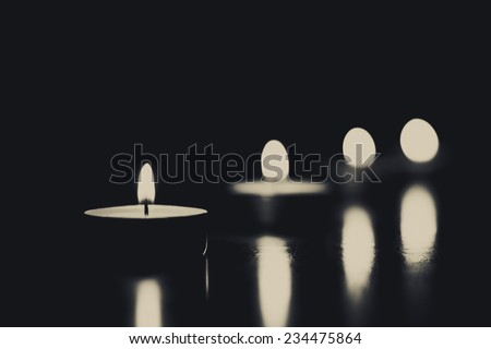 Closeup of burning candles on a black background - stock photo