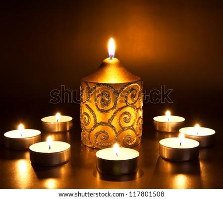 Closeup of burning candles on dark background - stock photo